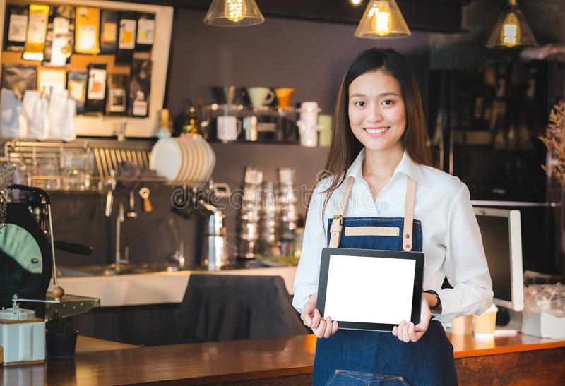Smiling asian woman barista holding blank tablet compute in front of coffee shop counter bar,Mock up space for display of menu or. Design,clipping path on stock image