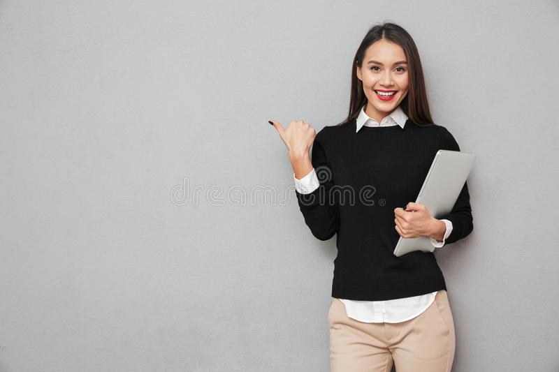 Smiling asian woman in business clothes holding laptop computer royalty free stock photography