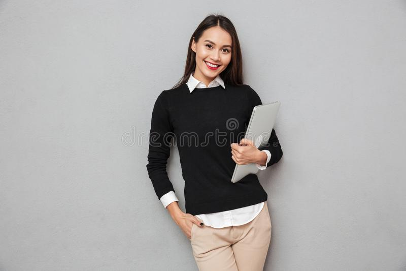 Smiling asian woman in business clothes holding laptop computer. While looking at the camera over gray background stock photo
