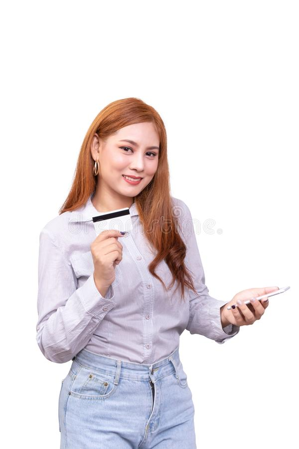 Smiling Asian woman in casual shirt holding mobile phone and showing credit card for shopping online royalty free stock photography