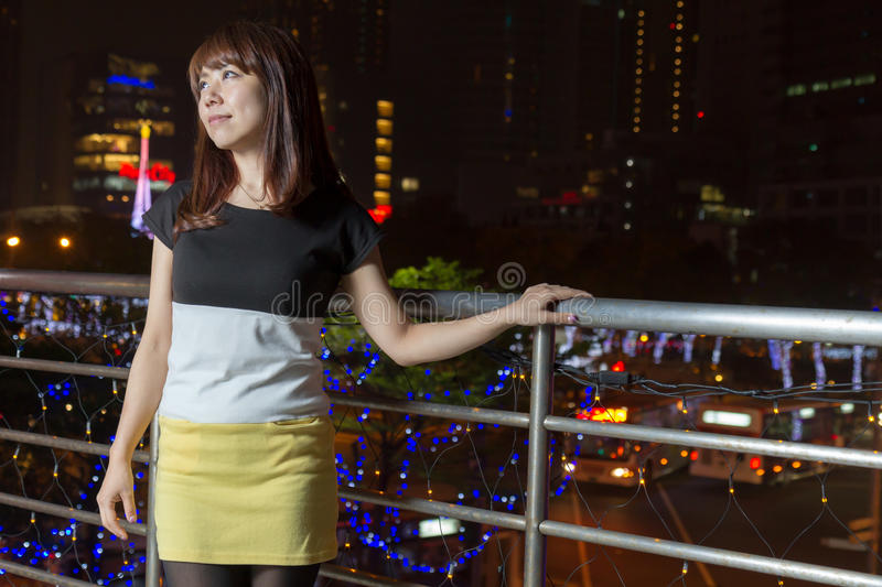 Smiling Asian woman in front of city lights stock photo