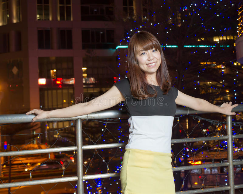 Smiling Asian woman in front of city lights royalty free stock photos