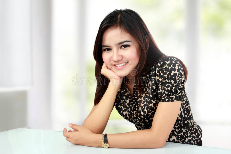 Smiling asian woman with hand on chin sitting stock photography