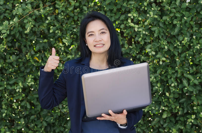 Smiling asian woman holding laptop and showing thumbs up front o stock images