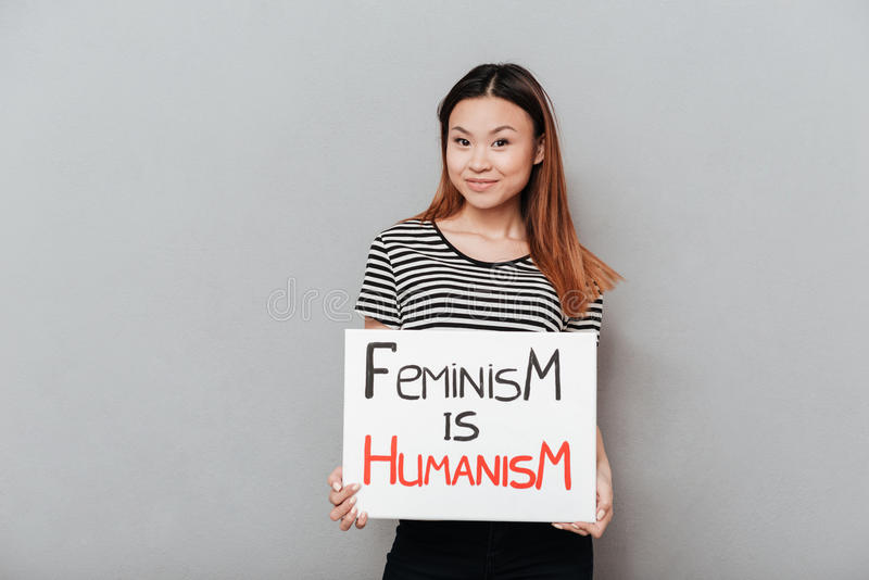 Smiling asian woman holding poster with slogan. Smiling asian feminist woman holding poster with slogan `Feminism is humanism` isolated stock images