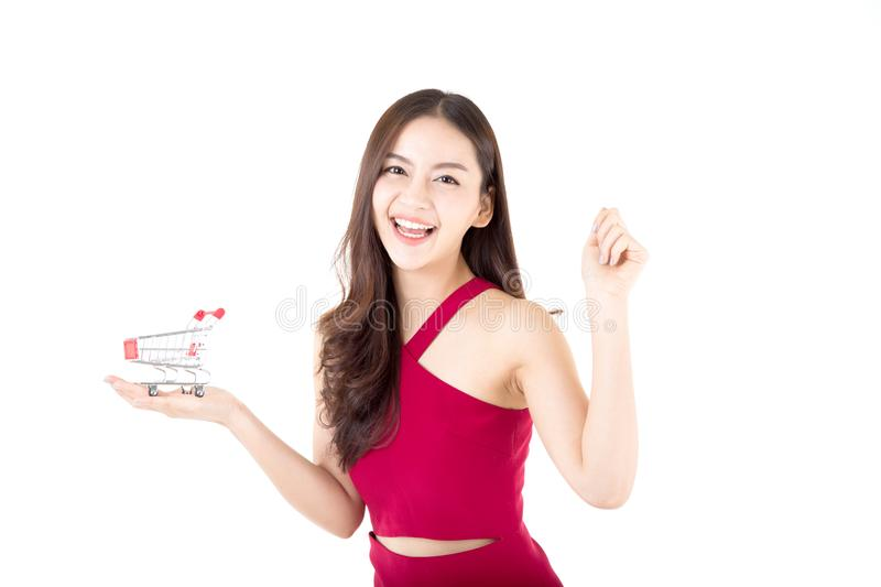 Smiling asian woman in red dress holding shopping cart with girl isolated. On white background, shopping online concept stock images