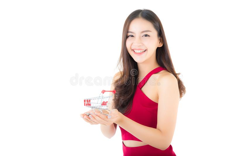 Smiling asian woman in red dress holding shopping cart with girl isolated. On white background, shopping online concept royalty free stock photography
