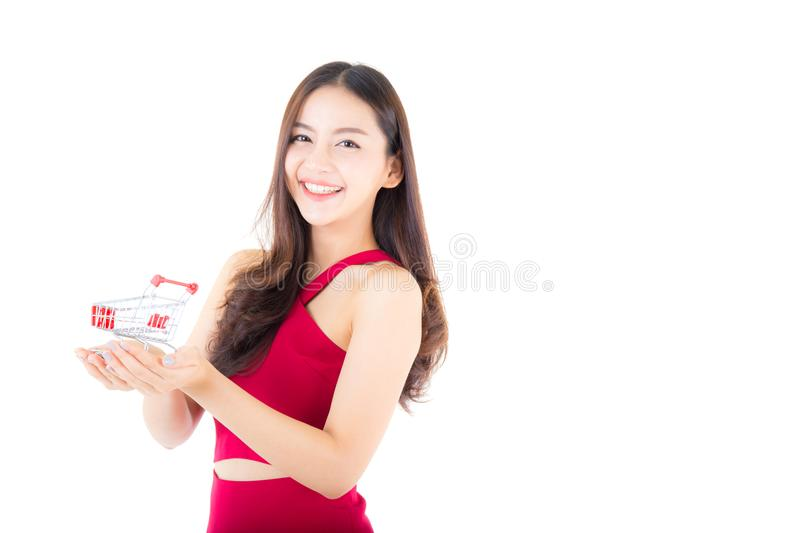 Smiling asian woman in red dress holding shopping cart royalty free stock photo