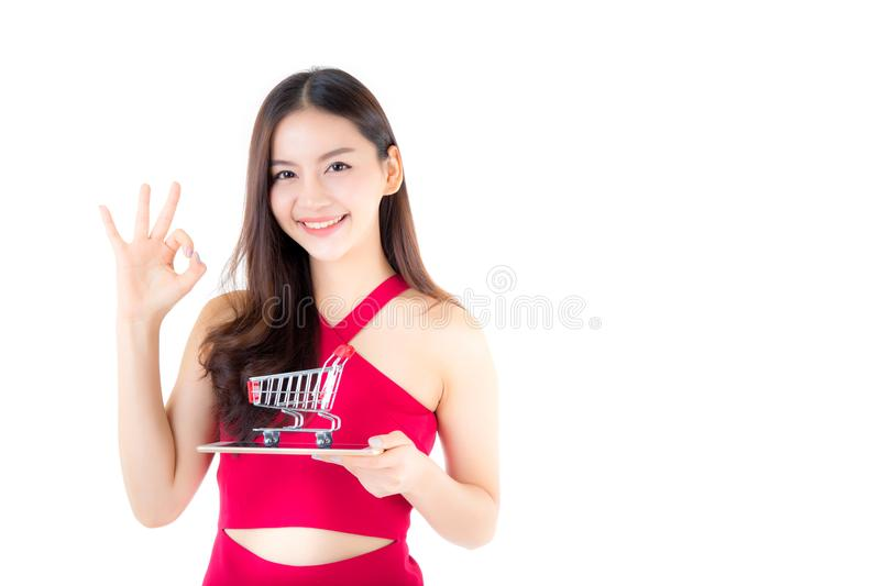 Smiling asian woman in red dress holding tablet with glad girl g royalty free stock photography