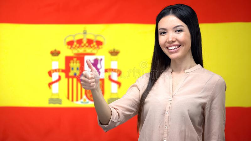 Smiling Asian woman showing thumbs-up gesture against Spanish flag background royalty free stock photos