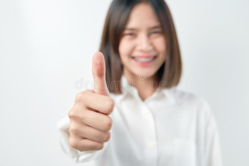 Smiling Asian woman and showing thumbs up or like on gray background. stock images