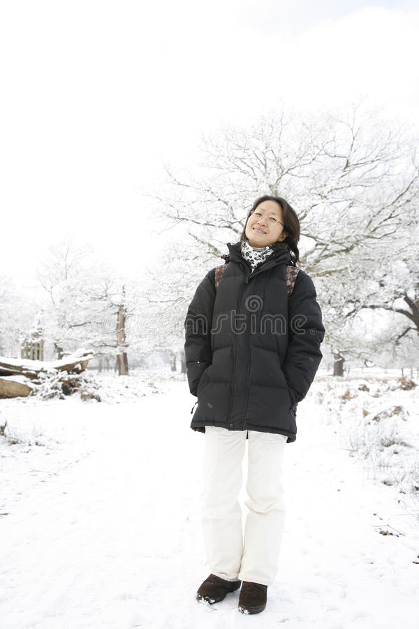 Smiling Asian Woman in snow covered Park. Smiling East Asian Woman Looking the Camera in snow covered Richmond Park stock images