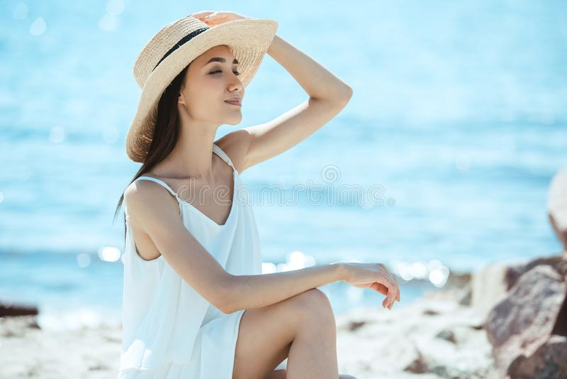smiling asian woman in straw hat and white dress stock photo