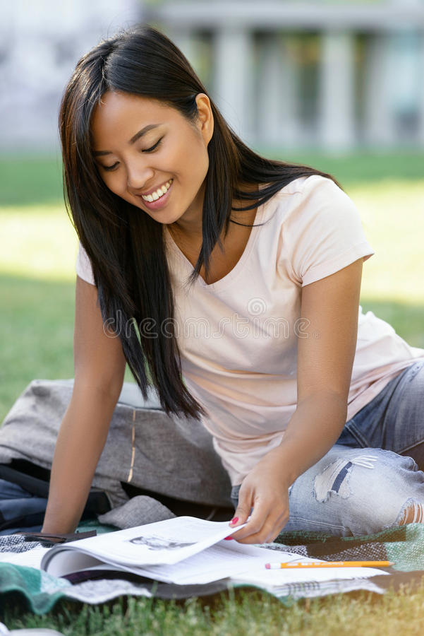 Smiling asian woman student studying outdoors. Looking aside. stock photos