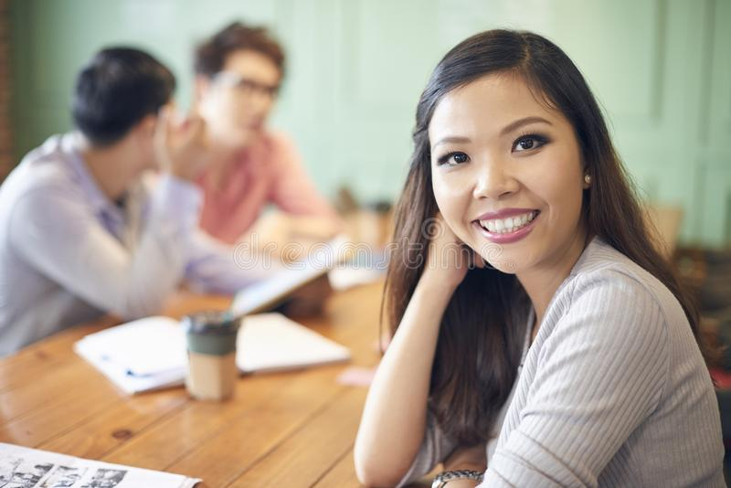Smiling Asian woman at table stock photography