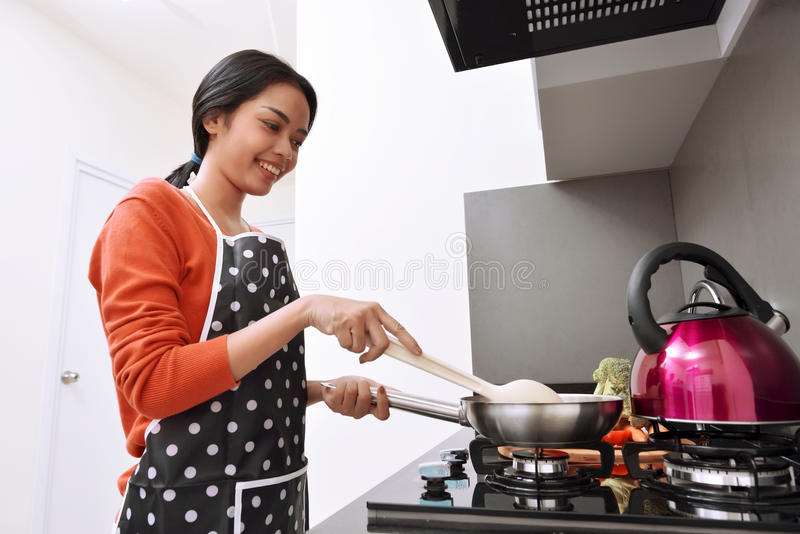 Smiling asian woman using frying pan and cooking stock photography