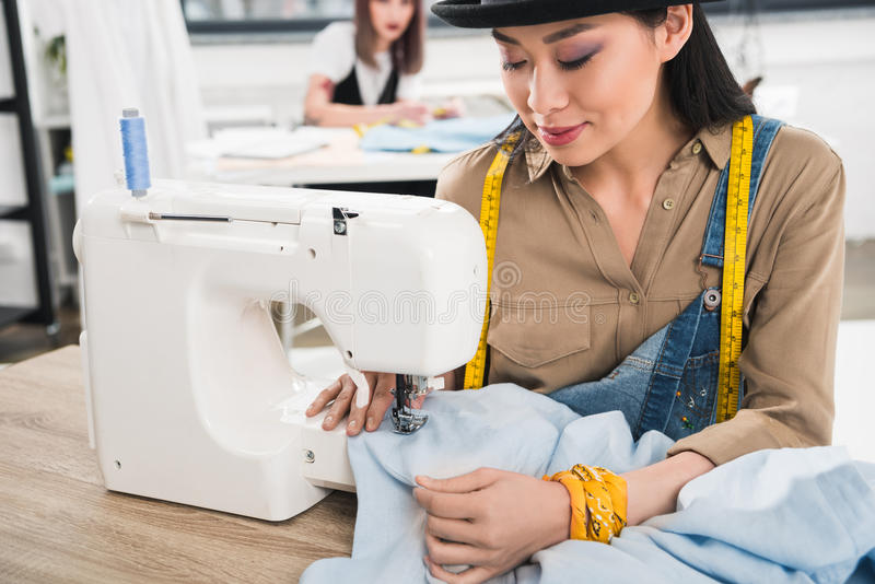 Smiling asian woman working with sewing machine stock image
