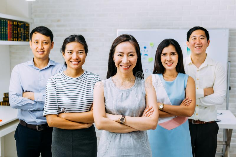 Smiling Asian young business people in casual wear standing in line with arms folded in meeting room stock photo