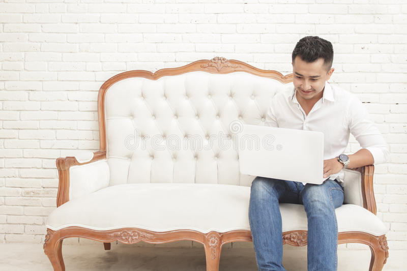 smiling asian young man sitting on sofa while watching and working on laptop at home royalty free stock photography