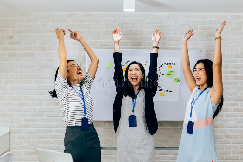 Smiling Asian young and mature business women standing in line with arms raised up gesture in meeting room with excited royalty free stock photography