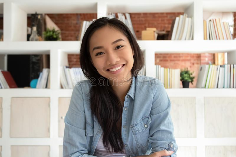 Smiling asian young woman looking at webcam making video call royalty free stock images