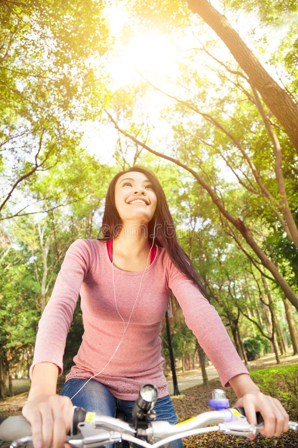 Smiling asian young woman riding bike in the forest royalty free stock photos