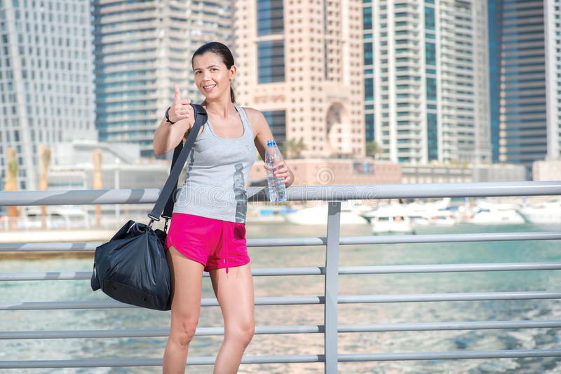 Smiling athlete shows thumb up. Athletic woman in sportswear hol royalty free stock image