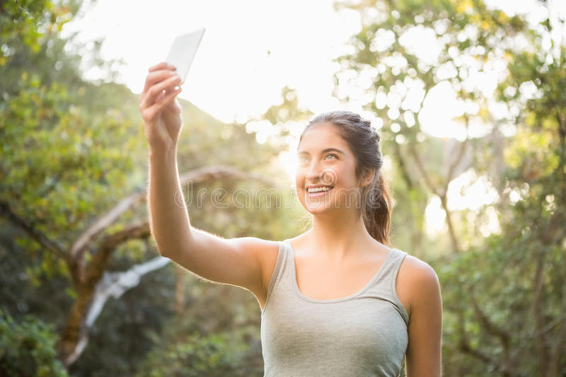Smiling athletic brunette taking selfies stock photography