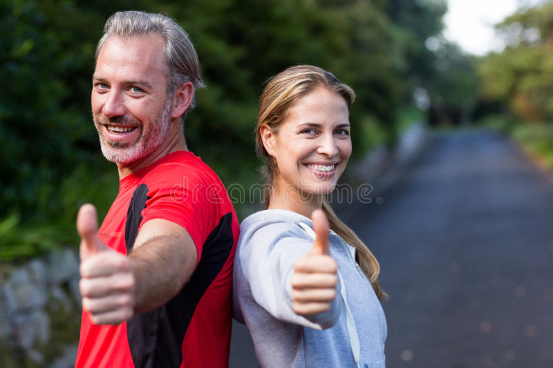 Smiling athletic couple showing thumbs up stock photo
