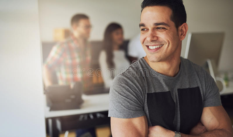 Smiling athletic man in office with co-workers stock photo