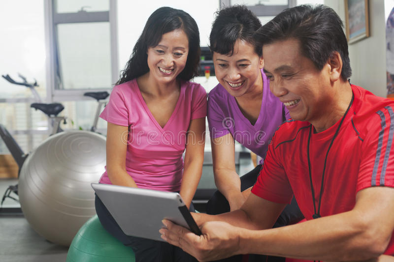 Smiling athletic people looking at digital tablet in the gym