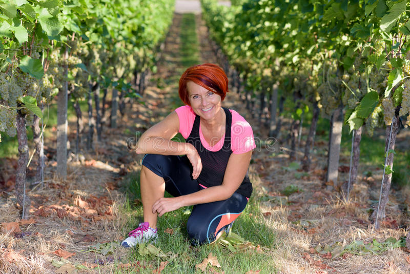 Smiling athletic woman kneeling in a vineyard royalty free stock photography