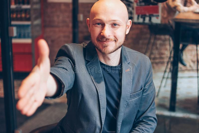 Smiling attractive adult successful bald bearded man in suit with laptop giving handshake, hand of help, greeting at cafe stock photography