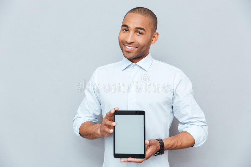 Smiling attractive african american young man holding blank screen tablet. Isolated royalty free stock photo