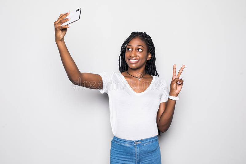 Smiling attractive african woman showing peace gesture and taking a selfie while standing isolated over gray background. Smiling attractive african woman showing royalty free stock photos