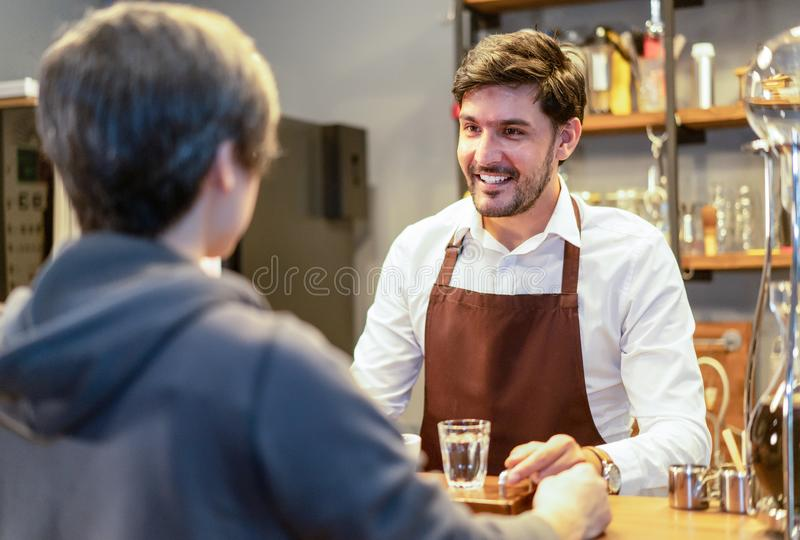 Smiling attractive bearded barista waiter standing behind counter giving  hot coffee to customer at cafeteria. Young entrepreneur royalty free stock photography
