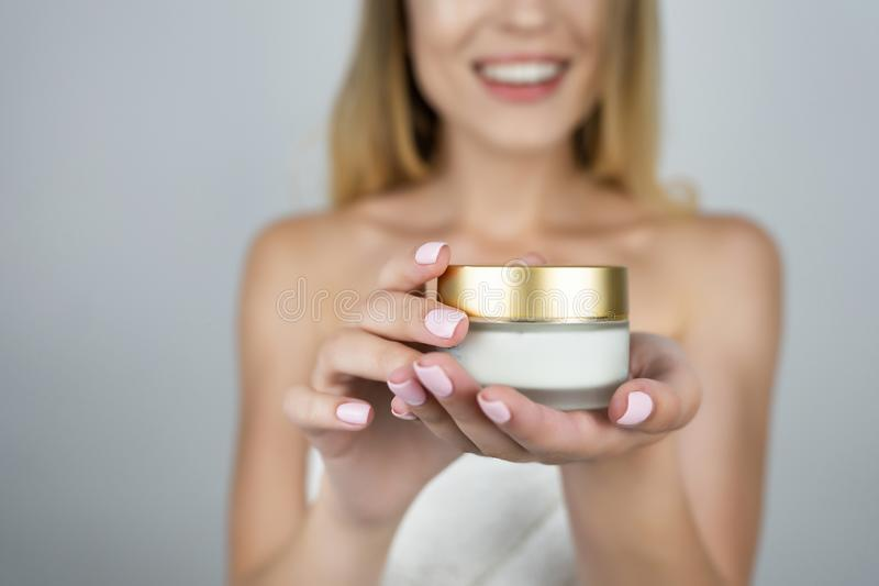 Smiling attractive blond woman holding beauty cream in her hands close up isolated white background royalty free stock photography