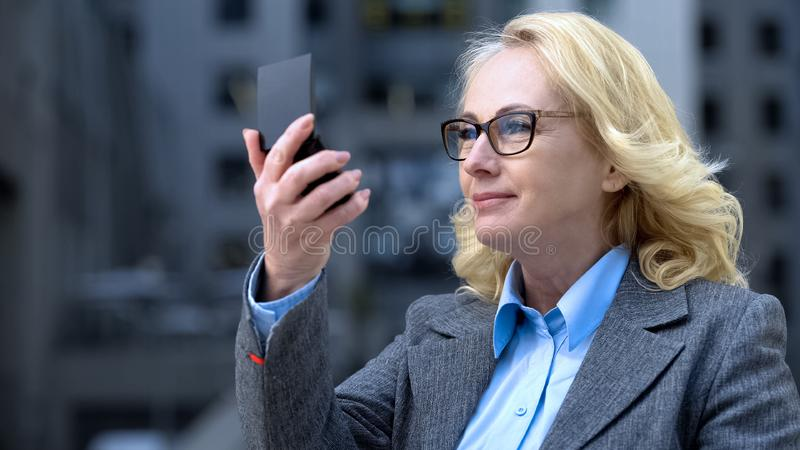 Smiling attractive business woman looking small mirror, anti-age skin care royalty free stock images