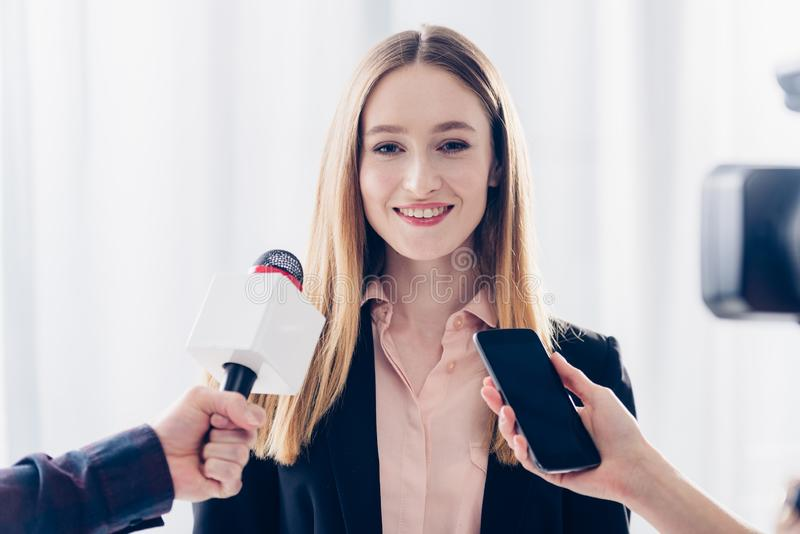 Smiling attractive businesswoman giving interview to journalists. In office royalty free stock photo