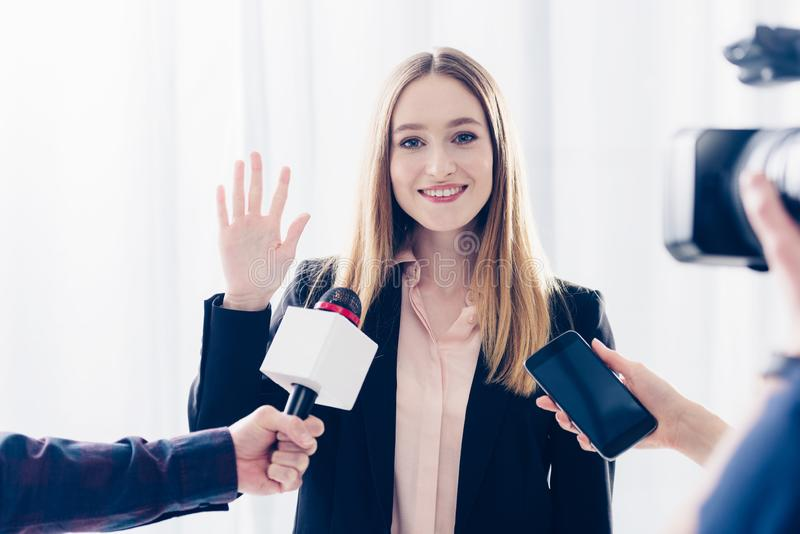 Smiling attractive businesswoman giving interview to journalists and waving hand. In office stock photography