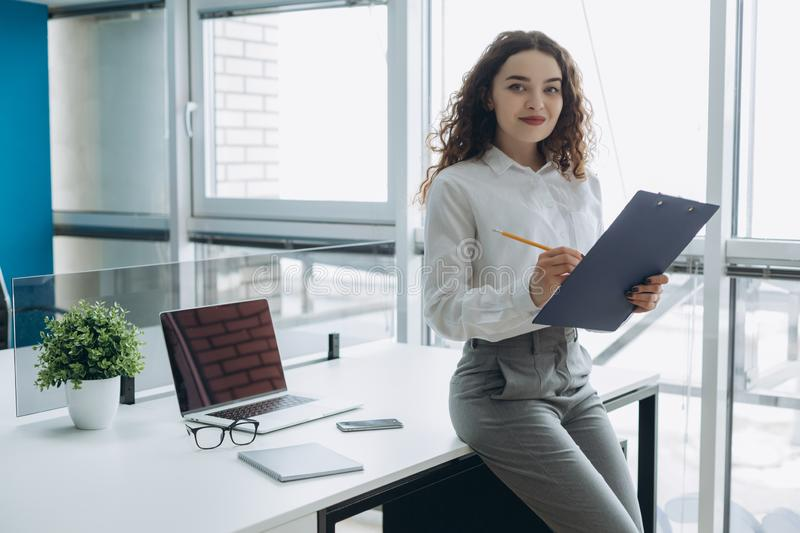 Smiling attractive businesswoman holding clipboard and looking at camera in office.  royalty free stock images