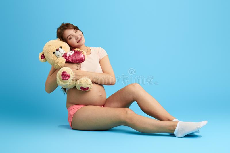 Smiling attractive girl hugging, embracing her toy royalty free stock photo