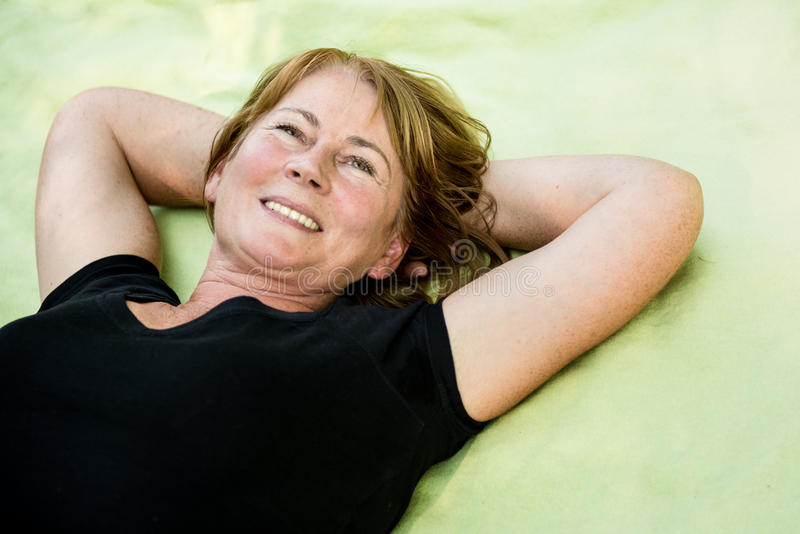 Smiling mature woman lying outdoor stock images