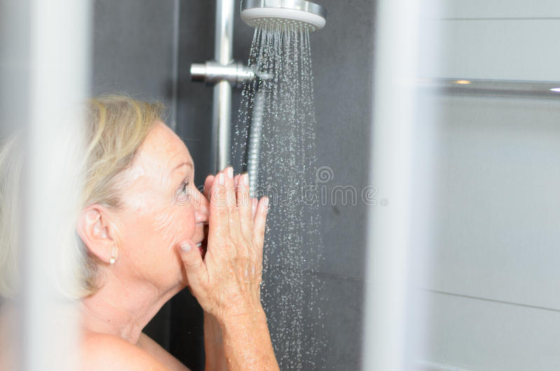 Smiling attractive senior woman taking a shower stock image