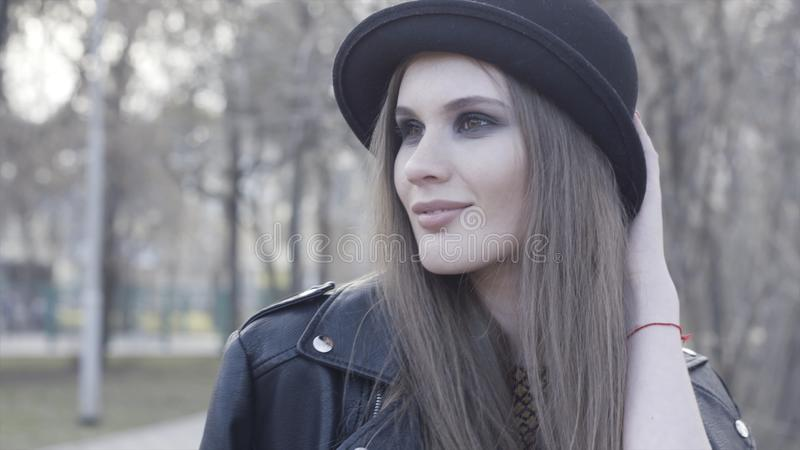 Smiling attractive stylish girl with smoky eyeshadow wearing black hat and leather jacket. Action. Young adorable royalty free stock images
