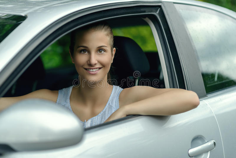 Smiling attractive woman driving a car stock photos