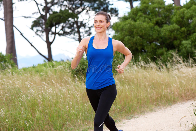Smiling attractive woman speed walking royalty free stock images