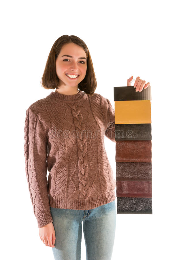 Smiling attractive woman in sweater holding fabric swatches. Isolated on white background stock image