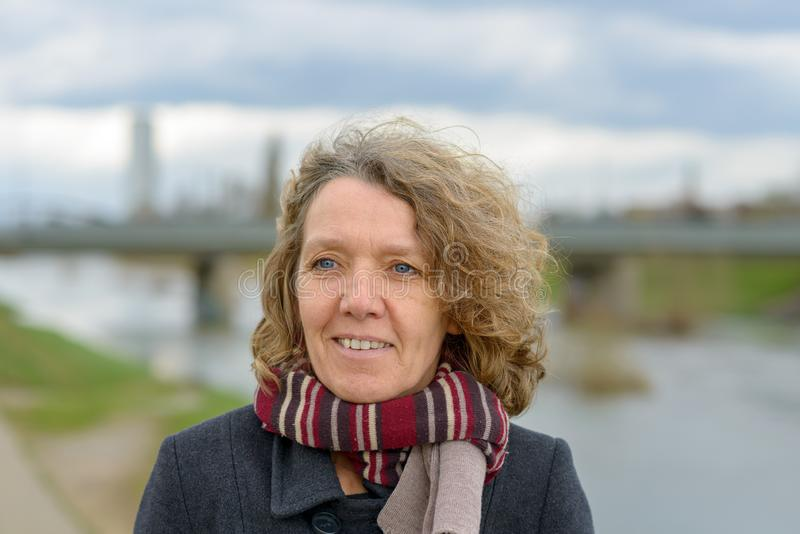 Smiling attractive woman with tousled curly hair. Wearing a warm winter coat and scarf posing outdoors on a grey day near a river stock photography