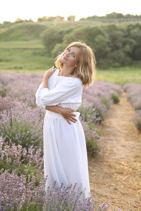 Smiling attractive woman in white dress hugging herself in violet lavender. Field stock images